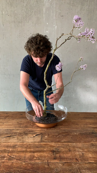 @the_ikebana_project placing the first branch on the kenzan in the NUDE Contour bowl for the Ikebana project