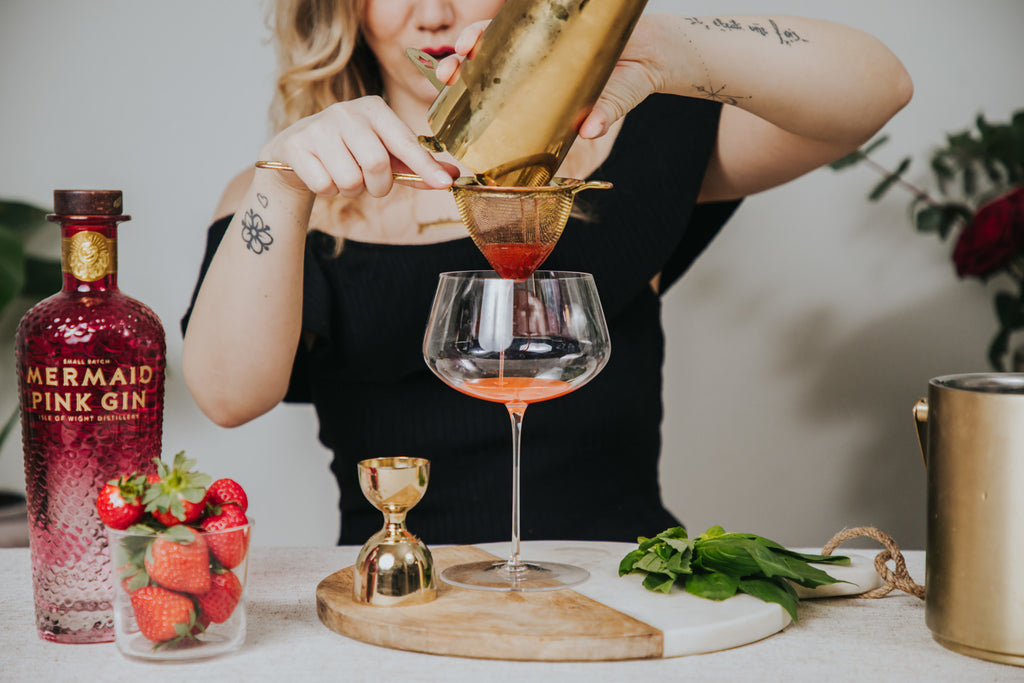 Camille Vidal creating the low abv cocktail, based on pink gin, strawberries and basil, in a NUDE Glass Stem Zero glass.