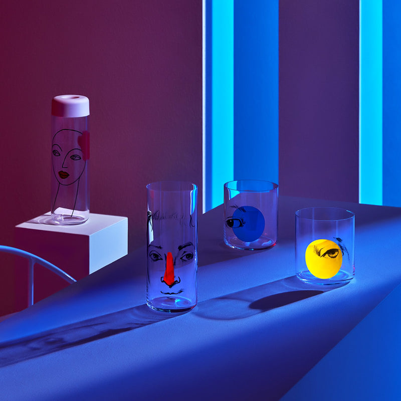 Lifestyle image of NUDE Rock & Pop glass collection with jug, highball glass and whisky glass in light neon environment