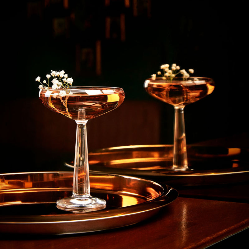 NUDE Big Top Coupe glass with linear patterned stem with elegant cocktail presented on a bar