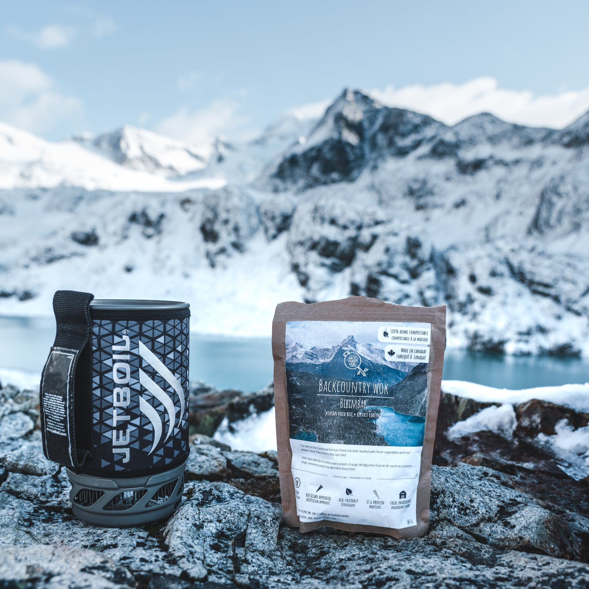 A package of Backcountry Wok's meals backdropped by snowcapped mountains.