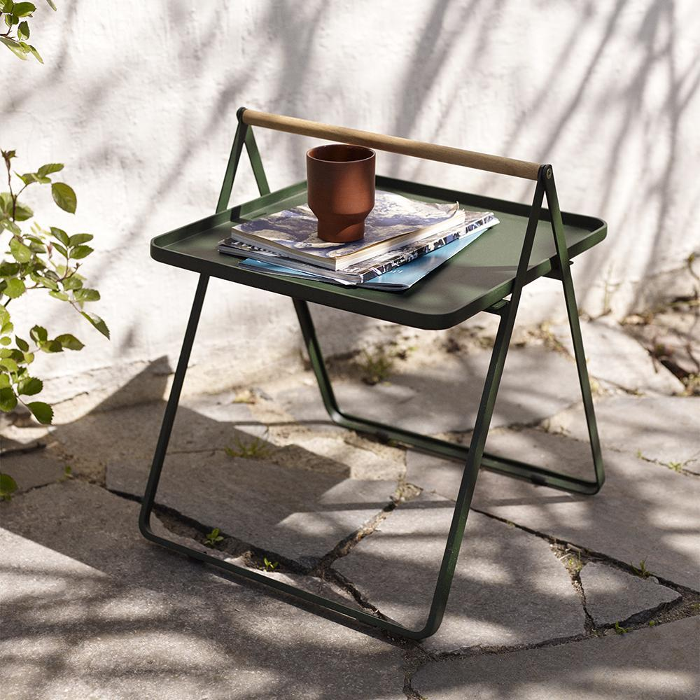 A small green outdoor table stacked with magazines and a ceramic cup