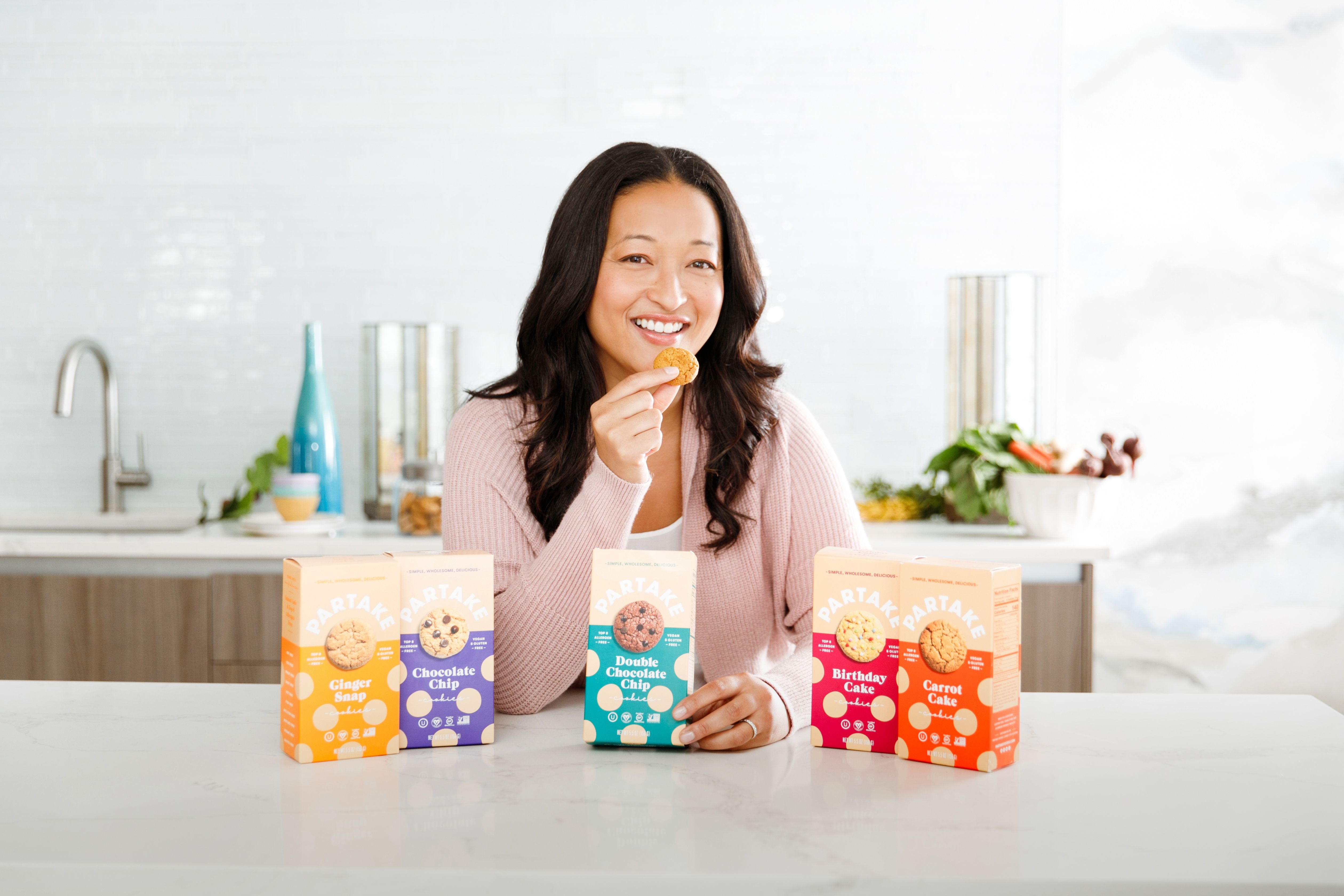 Denise Woodard in a kitchen with five different types of Partake Foods cookies displayed in front of her.