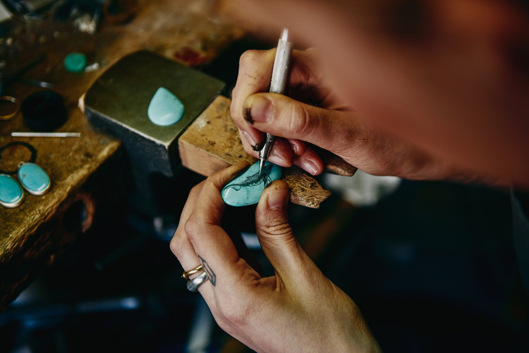 76cac5b42244 Close up image of jewelry designer Hannah Blount s hands as she carves an  intricate whale illustration