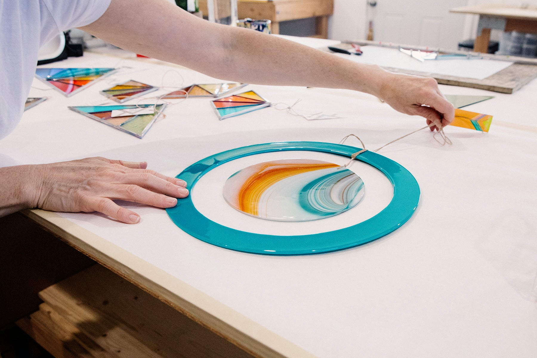 Detail photograph of Debbie Bean laying down a round, pale blue piece of stained glass with a string on top, in her studio.