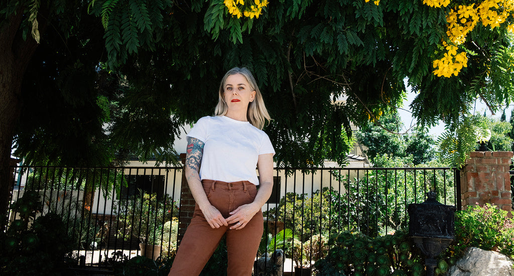 Portrait of the artist Debbie Bean standing under a tree with yellow flowers wearing a white t shirt and brown jeans with red lipstick on.