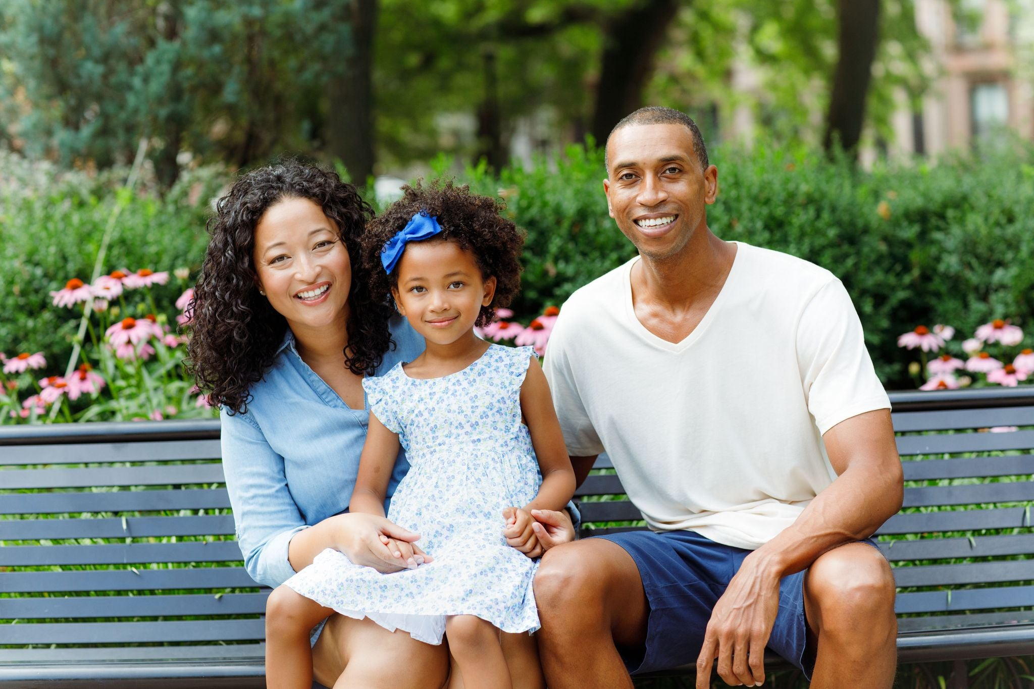 Denise Woodard and husband Jeremy with daughter Vivian sitting on a park bench backdropped by trees and flowers.