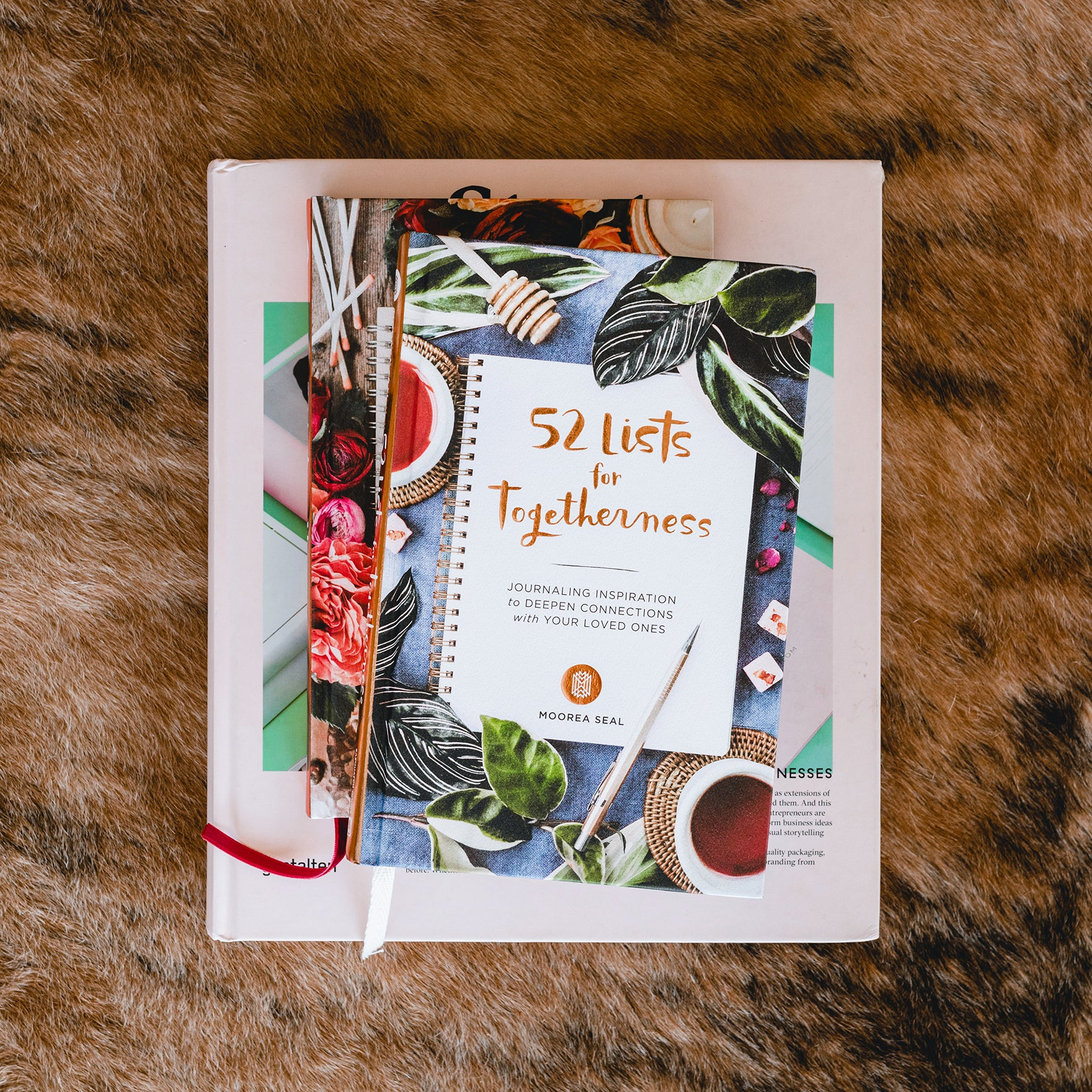 A book titled 52 Lists for Togetherness lays on a stack of books set upon a faux fur surface