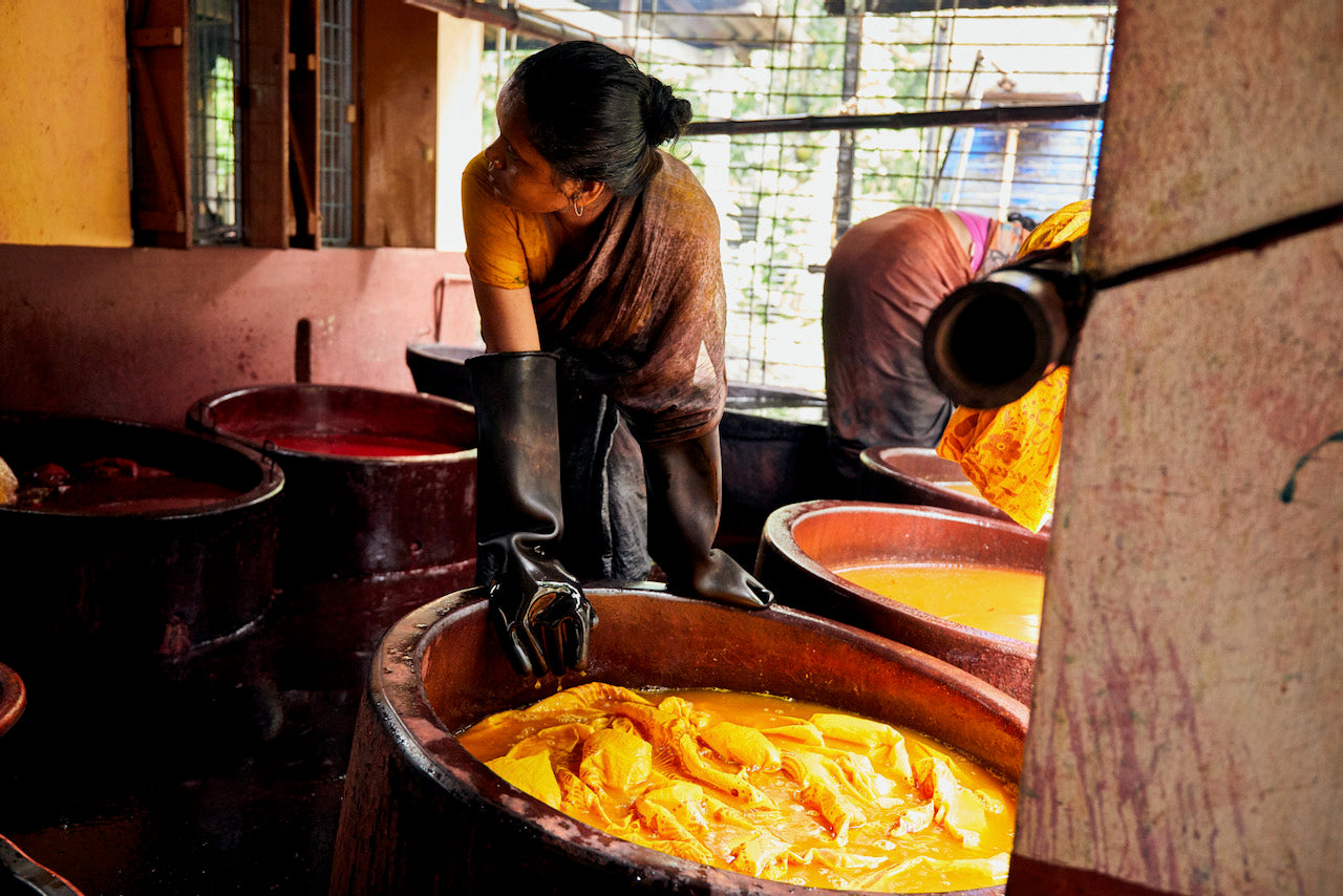 An artisan washes and dyes a saree fabric for Suta.