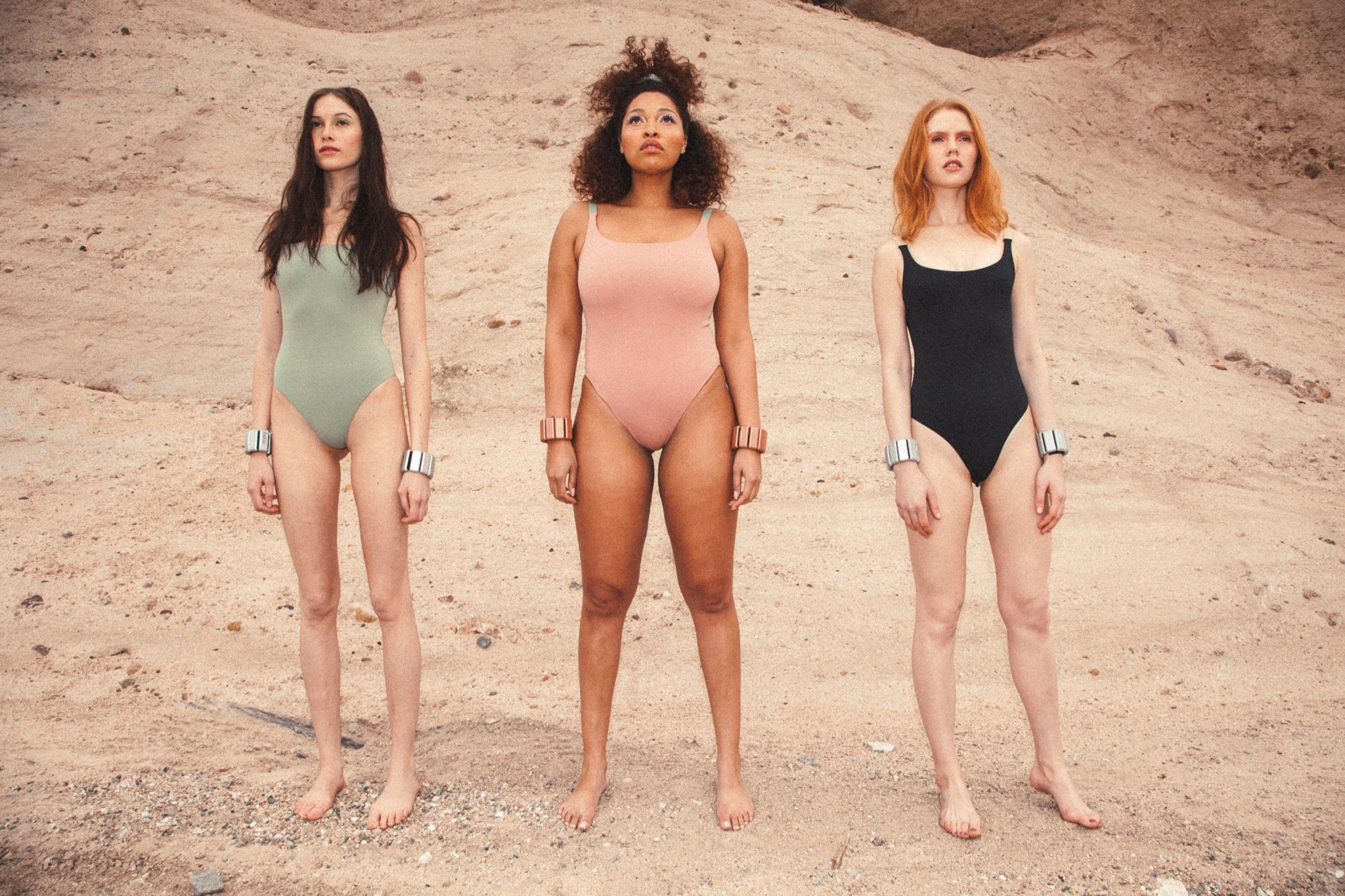 Three models wearing workout bodysuits and Bala Bangles in the desert.