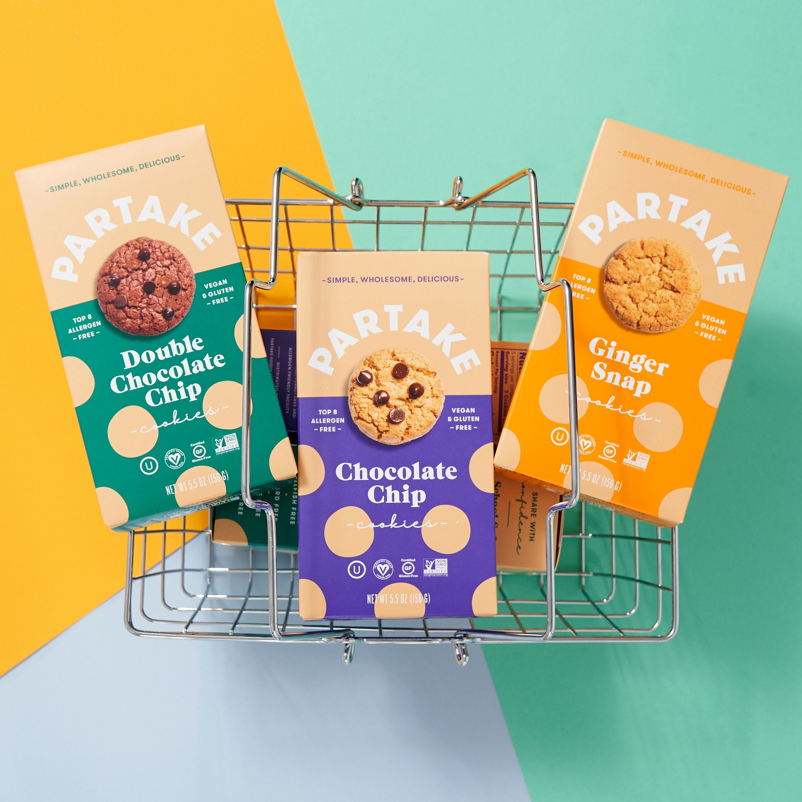 A trio of Partake Foods cookie boxes in the flavors of Double Chocolate Chip, Chocolate Chip, and Ginger Snap backdropped by a metal grocery basket.