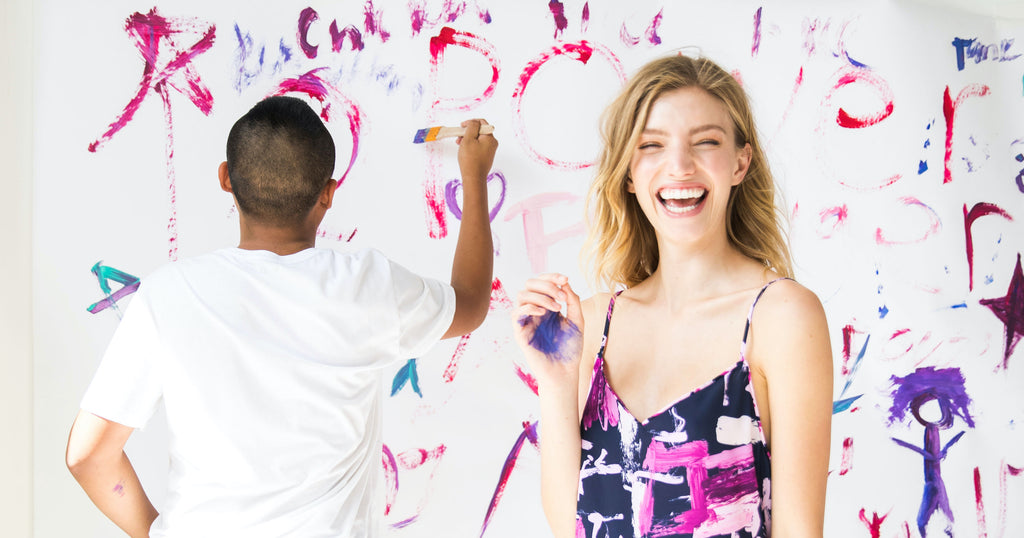 Woman in a printed dress laughs in the foreground while a man paints a wall behind her