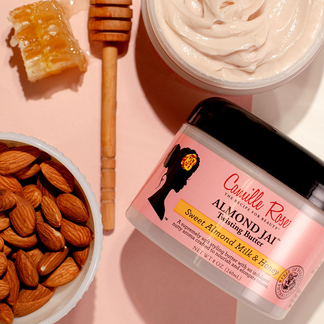 A jar of Camille Rose Almond Jai Twisting Butter along with raw almonds and honeycomb.