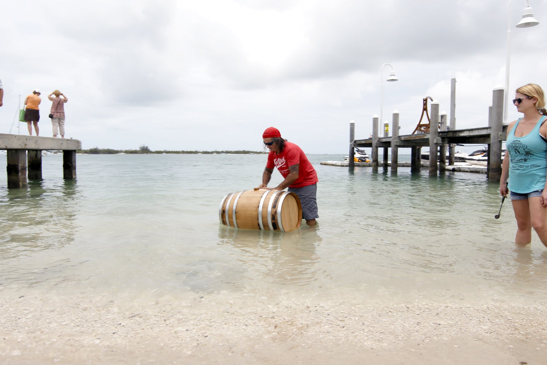 c589e2c97 Paul Menta of Key West Legal Rum Distillery submerges a wooden barrel in  the shallow salt