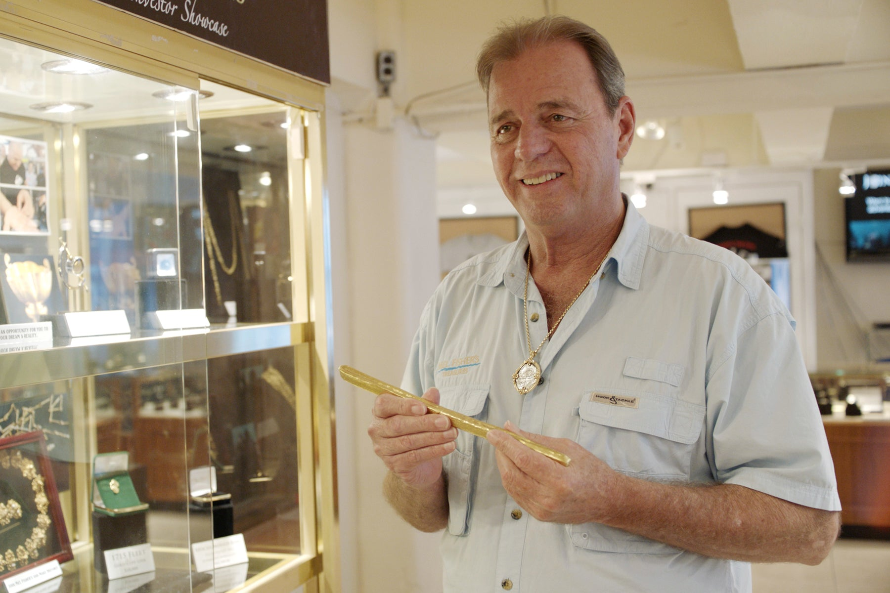 Kim Fisher, who operates Mel Fisher's Treasures in Key West, Florida holding a gold object next to a glass display cabinet filled with jewelry.