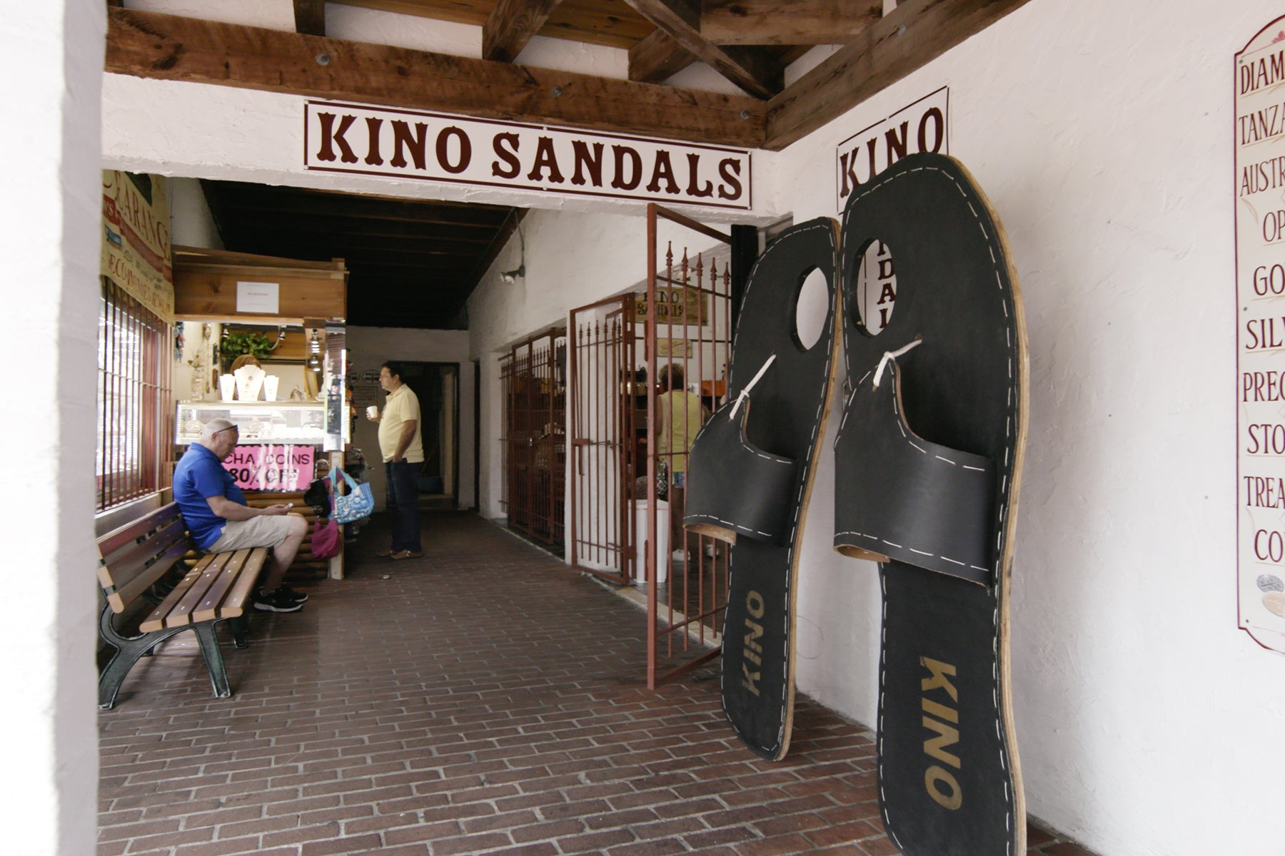 Exterior of Kino Sandals in Key West, Florida. Two oversized sandals lean on the wall by the shop's door.