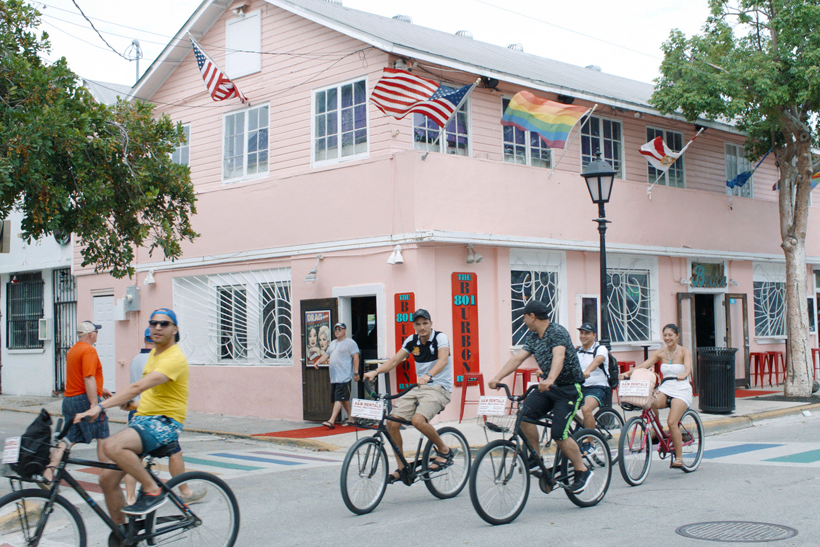 A group of people cycle past a pink building in Key West, Florida