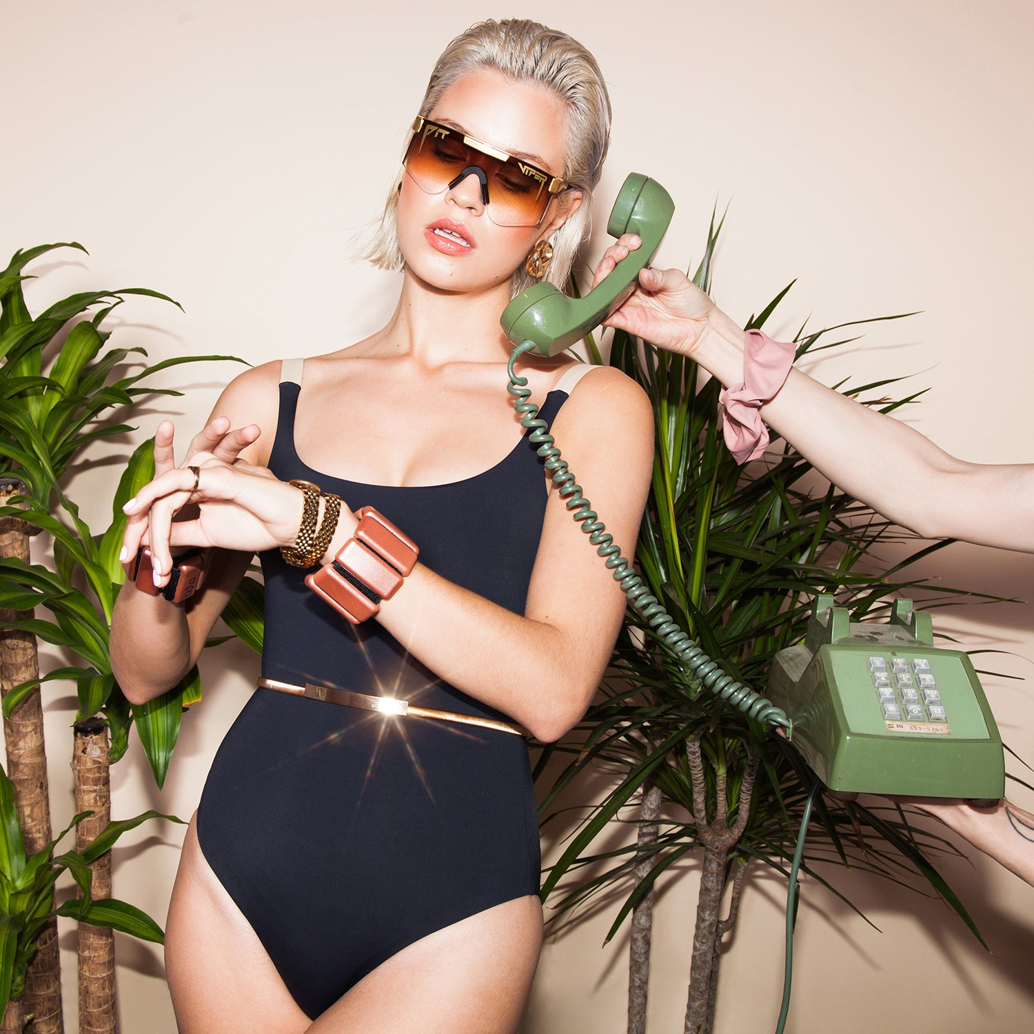 A model with sunglasses, in a workout bodysuit showcasing Bala Bangles while being on the phone.