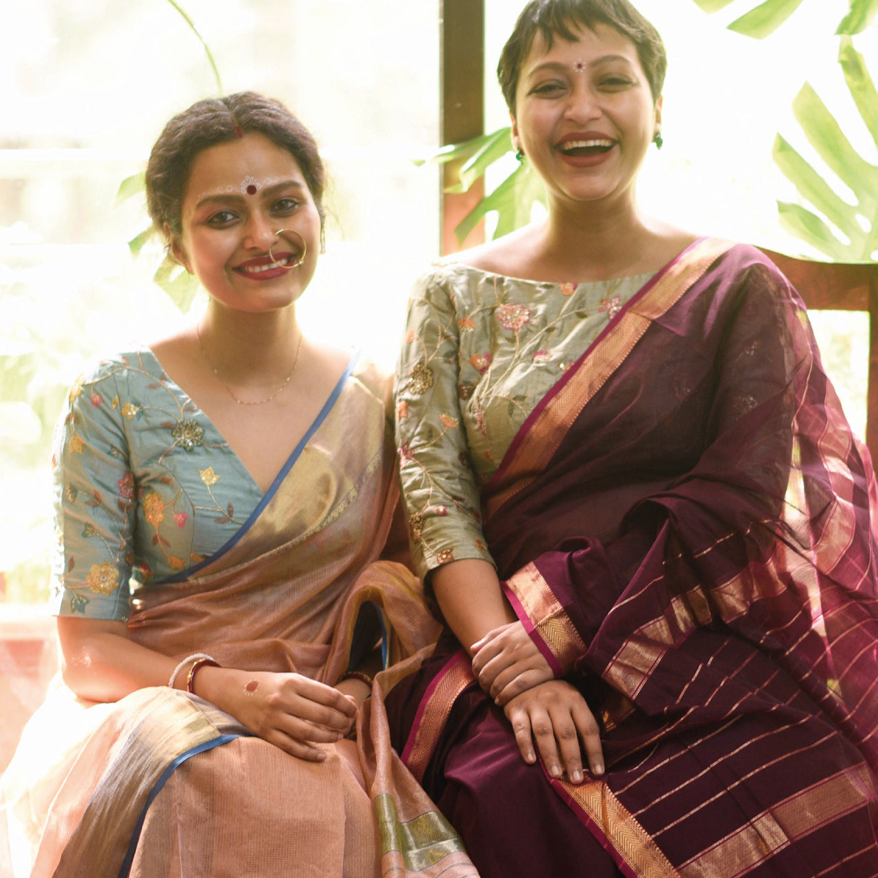 Sujata in a rose-colored saree, and Taniya in a maroon saree.