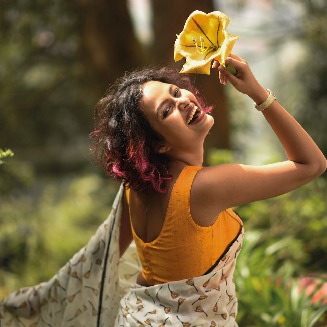 Sujata models a floral saree along with a bright yellow top.