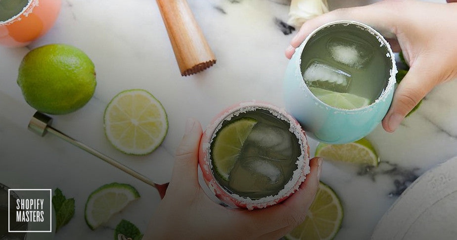 Overhead shot of two hands clinking drinks with ice and lime wedges inside the glass.