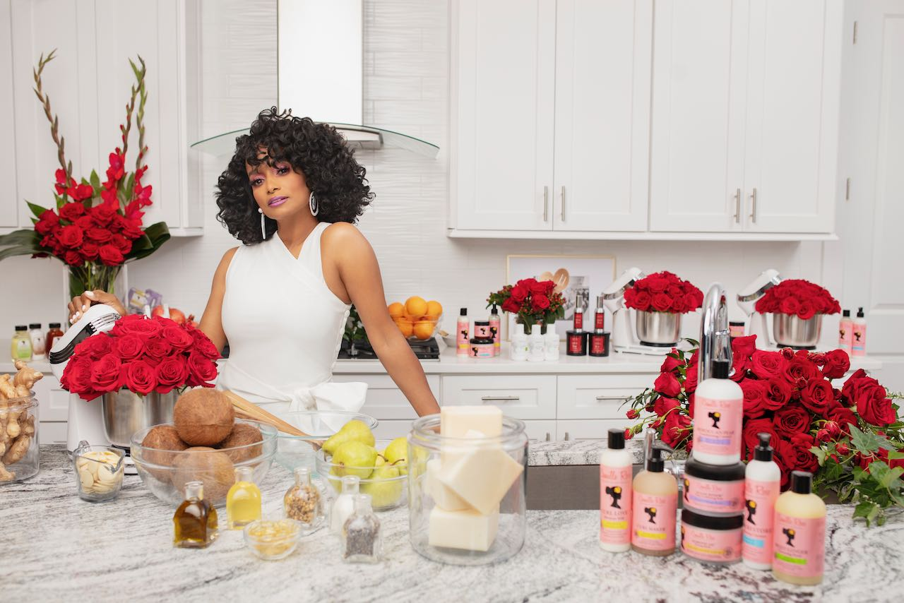 Janell Stephens in a white dress is surrounded by fresh ingredients and Camille Rose skincare products.