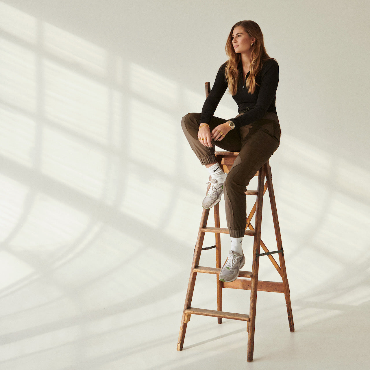 Camille Brinch sitting on top of a ladder wearing a dark top and olive pants while showcasing some of her rings, necklaces, and earrings.