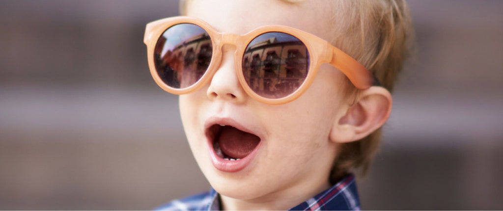 Excited kid wearing sunglasses looking cool