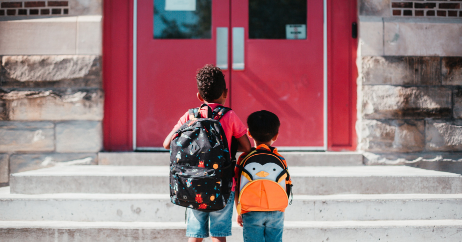 Two students with backpacks heading back into a school.