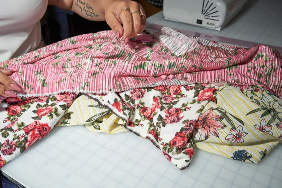 Close up of plus fashion designer Ashley Nell Tipton's hands, working with pink, floral fabric.