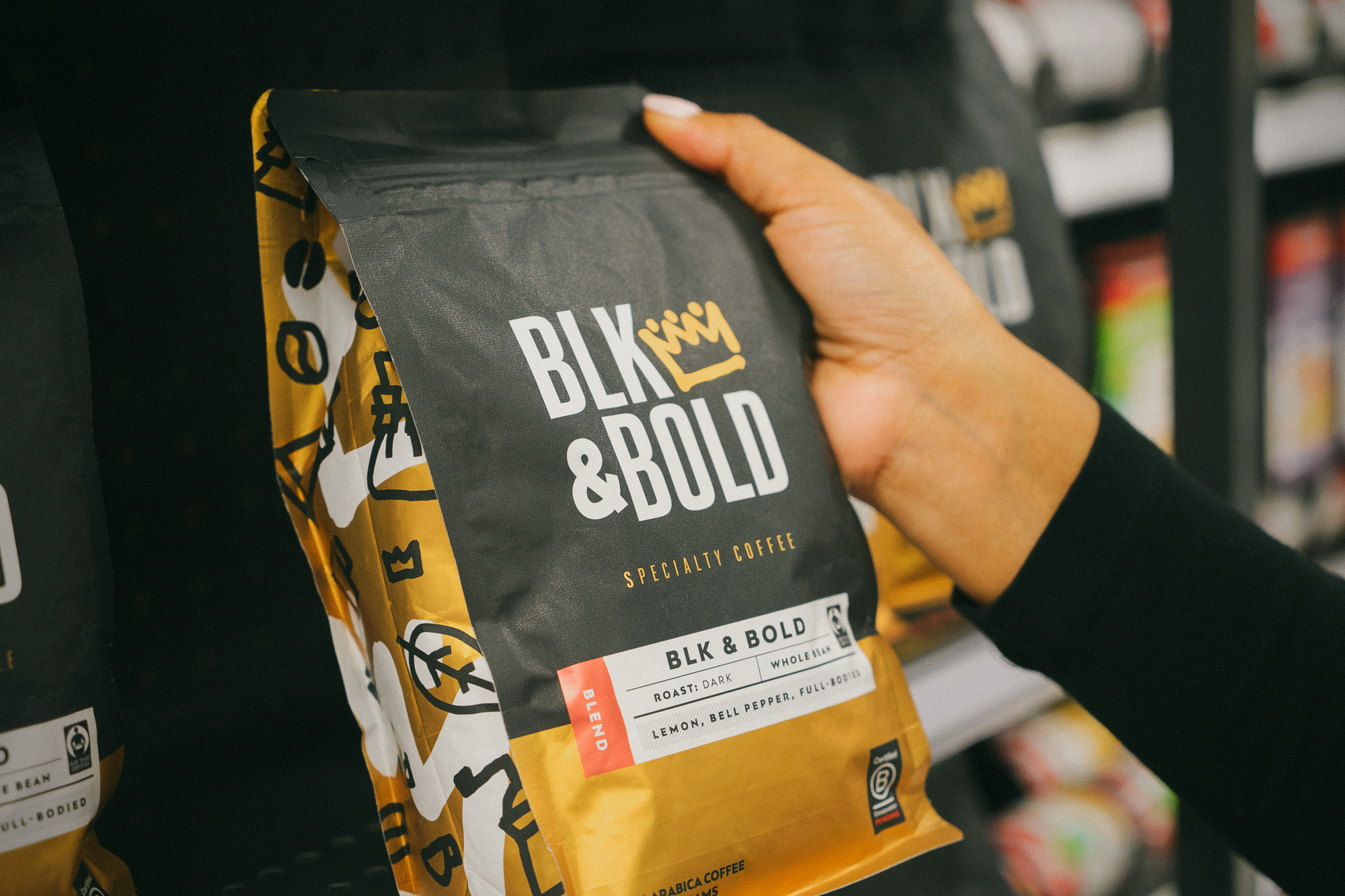 A package of BLK & Bold coffee held by a hand against some retail shelves.