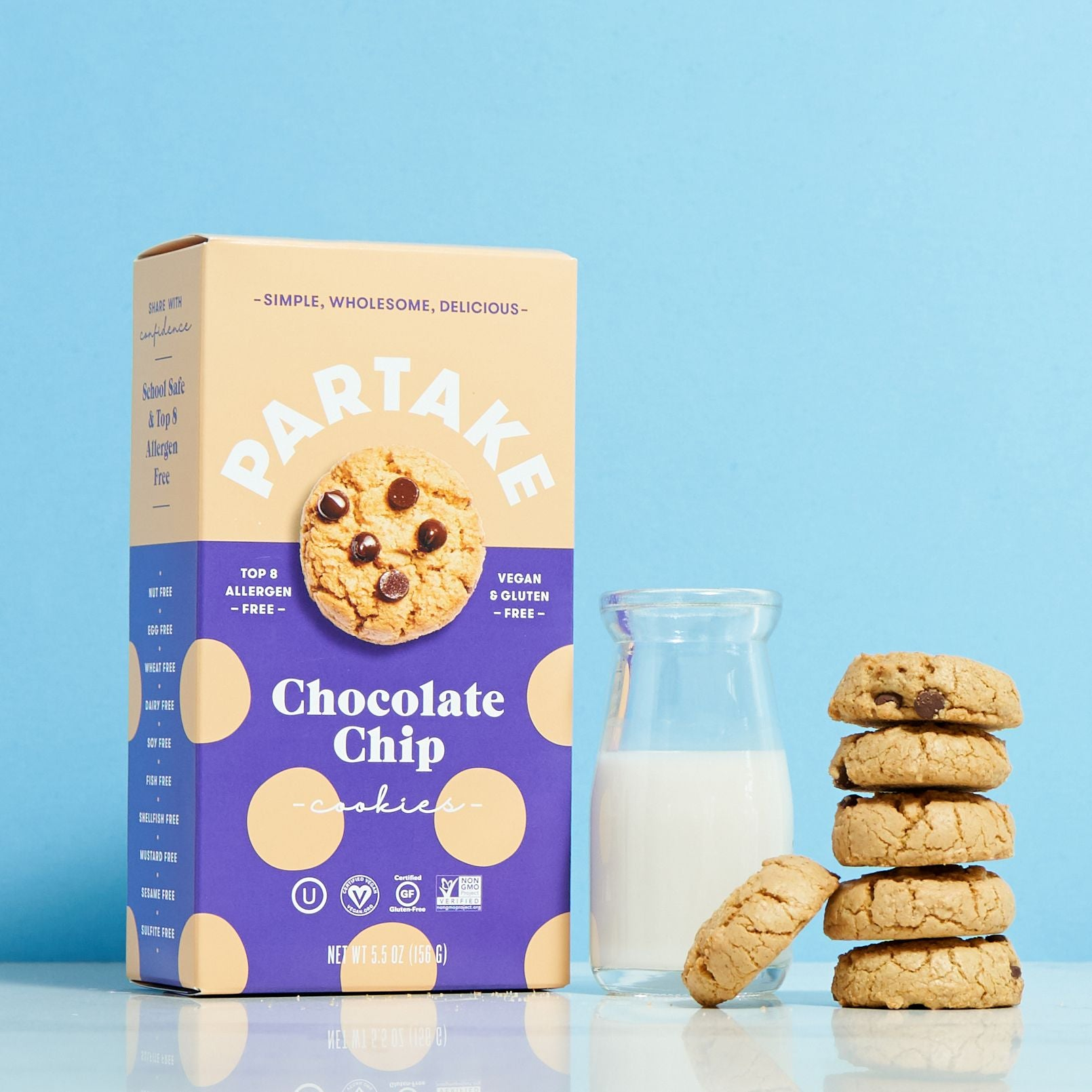 A box of Chocolate Chip cookies by Partake Foods along with a glass of milk and a stack of cookies displayed.