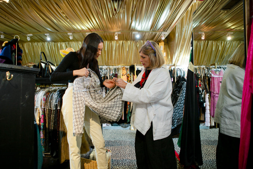 Shay Mitchell (left) holds up a black and white patterned blazer as Doris Raymond, owner of The Way We Wore, (right) shows her a detail at the hem.