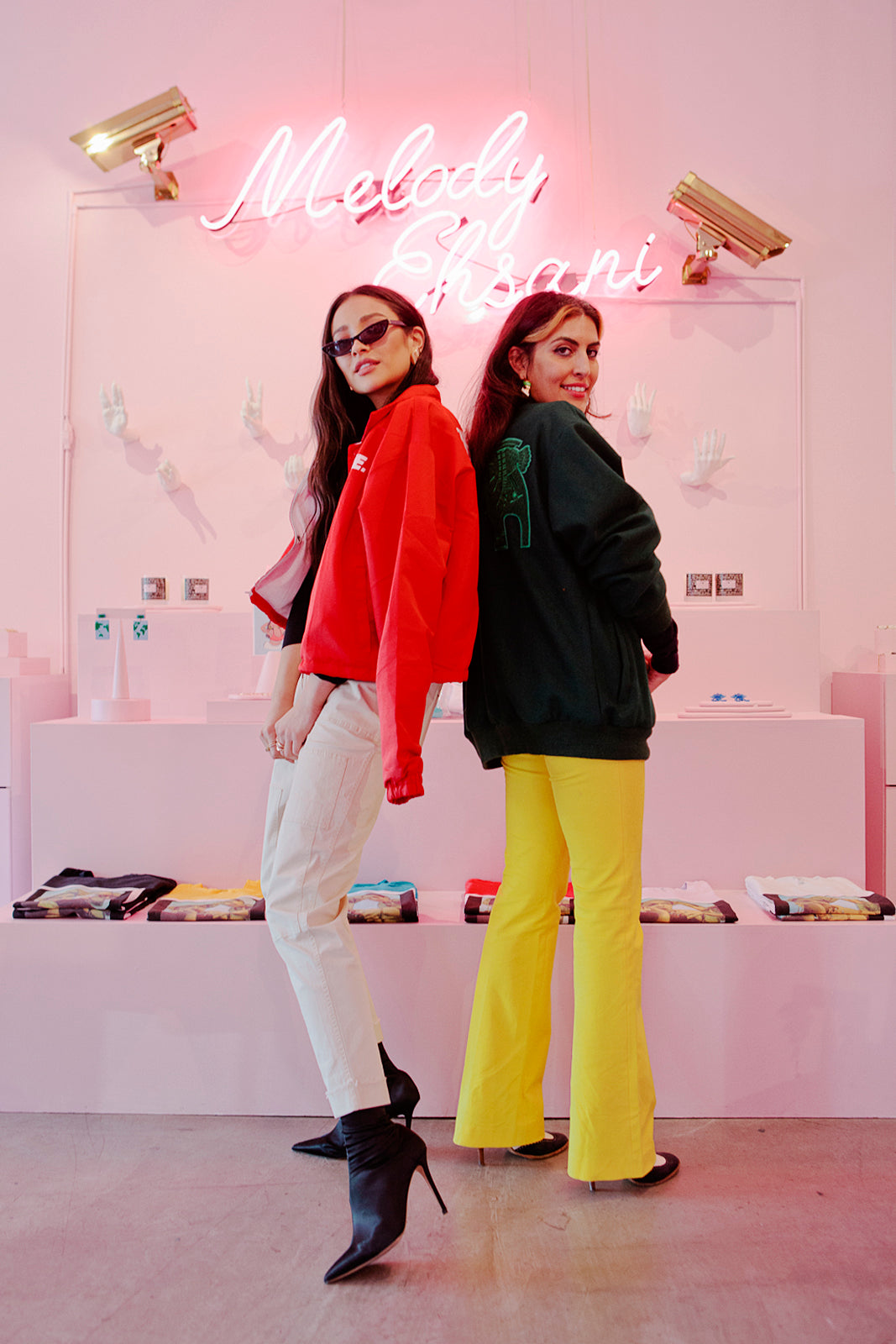 Shay Mitchell, in a red jacket and white pants (left), poses back to back with with Melody Ehsani (right), who's wearing a dark green jacket and yellow pants.