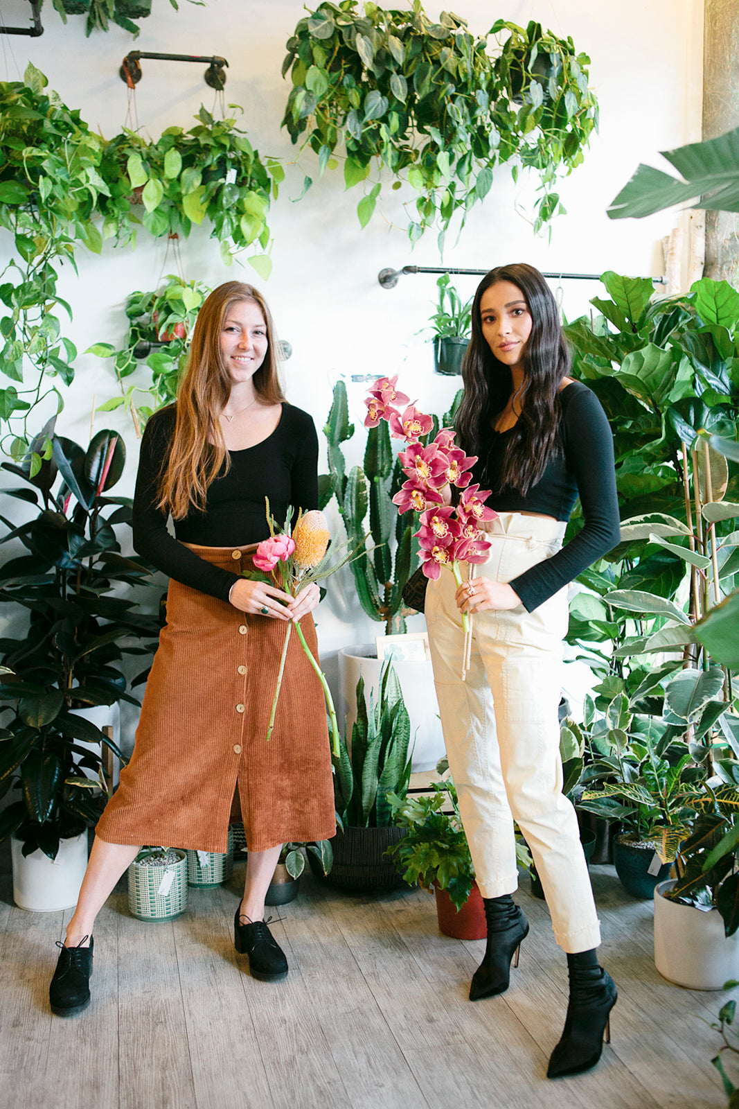 Alexandra Scholtz (left), owner of WildFlora, and Shay Mitchell (right), pose with flowers in front of a plant-filled wall.