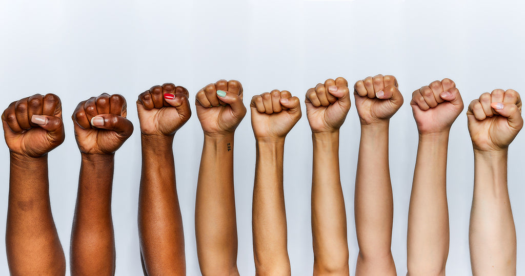 Photograph of 9 women's fists in the air starting from the darkest complexion and transitioning to the lightest complexion.
