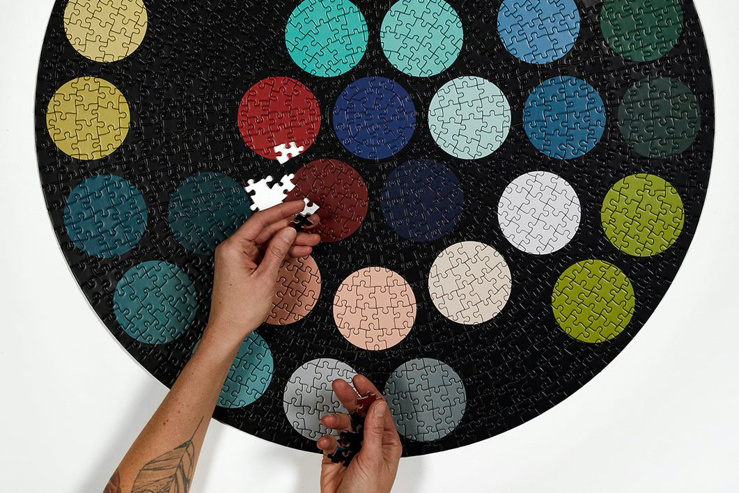 Hands place pieces into a large round puzzle