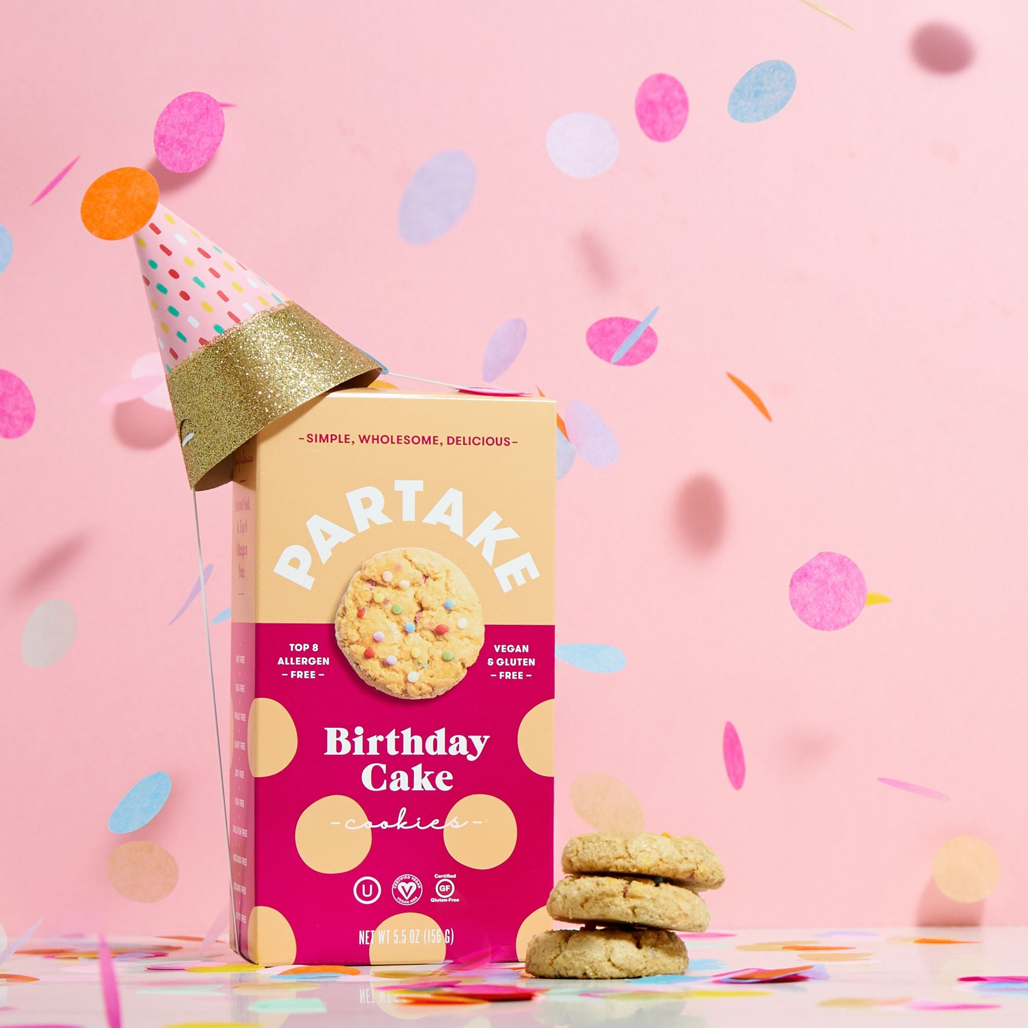A box of Birthday Cake cookies topped with a party hat with confetti in the photo along with three cookies outside of the box.