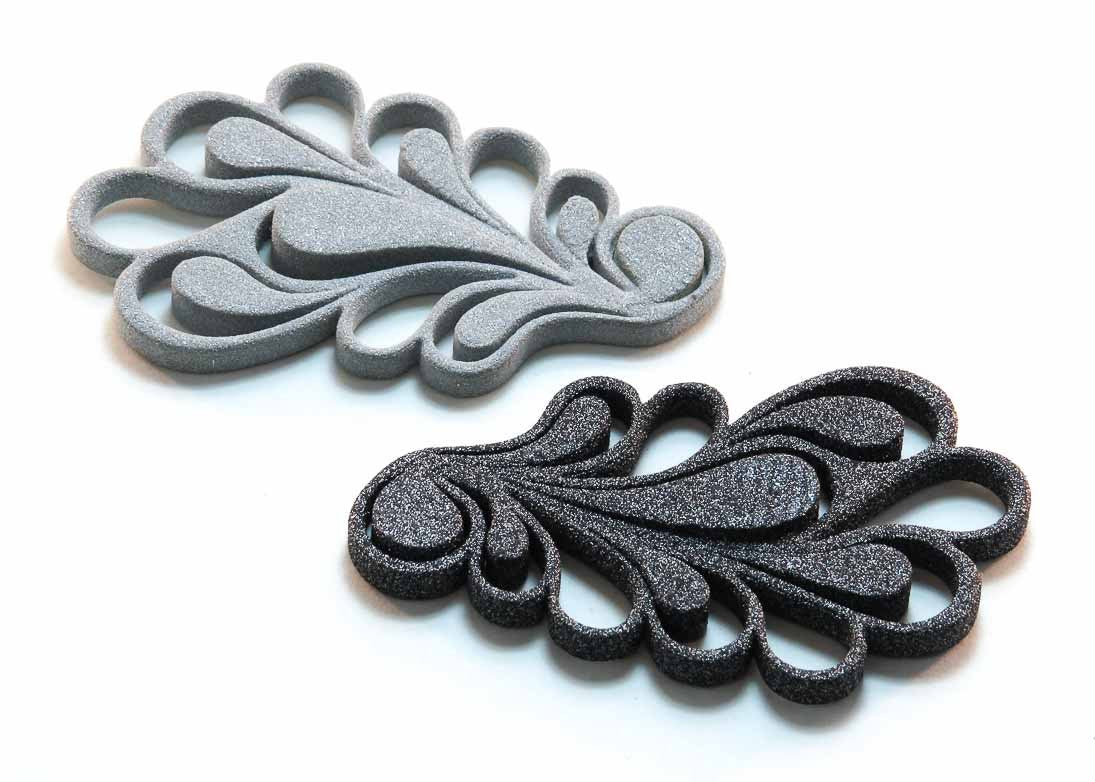 Two swirly 3D-printed earrings on a white surface