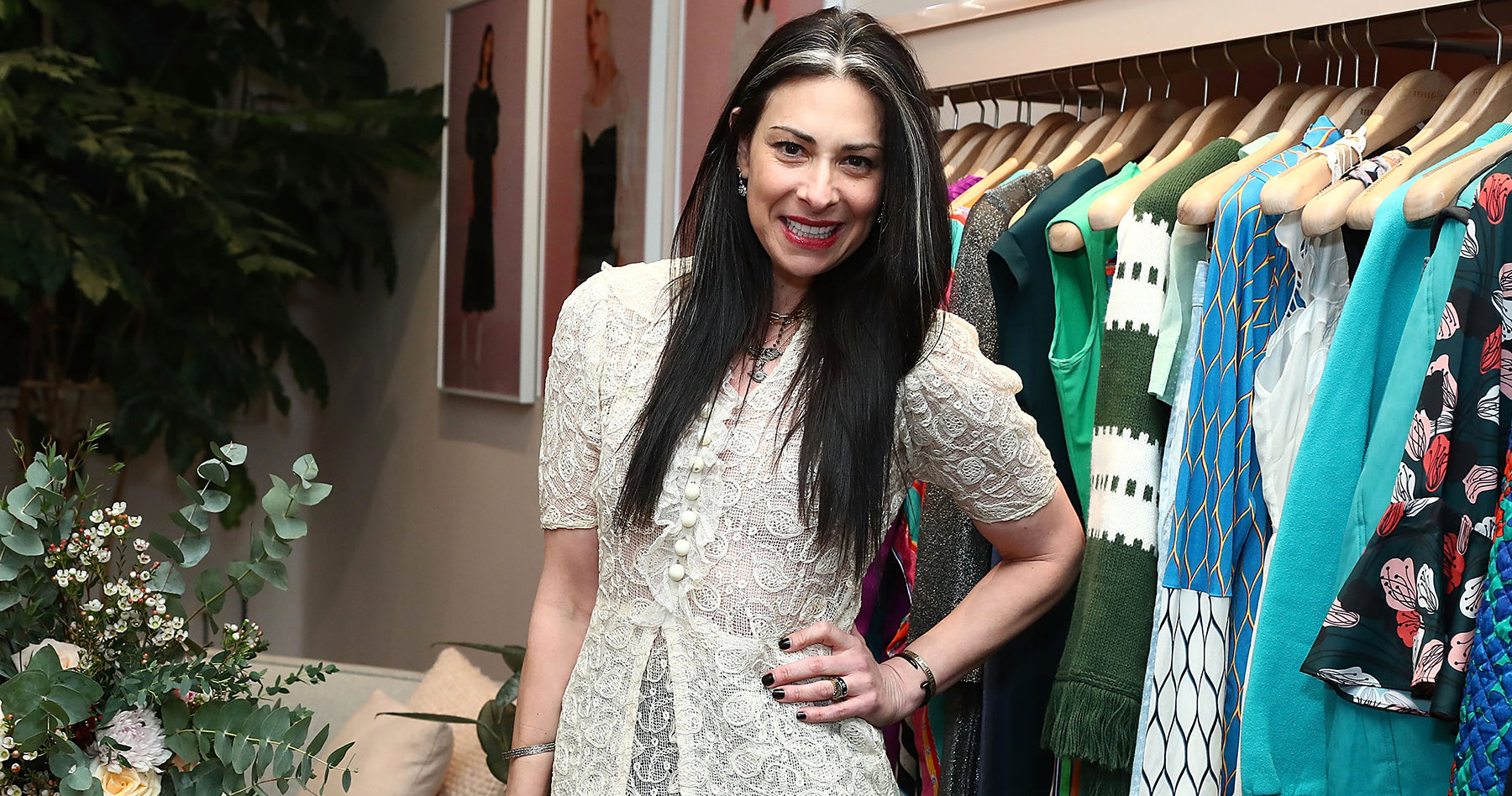 Portrait of Stacy London smiling at the camera standing in front of a rolling rack of clothes with one hand on her hip.