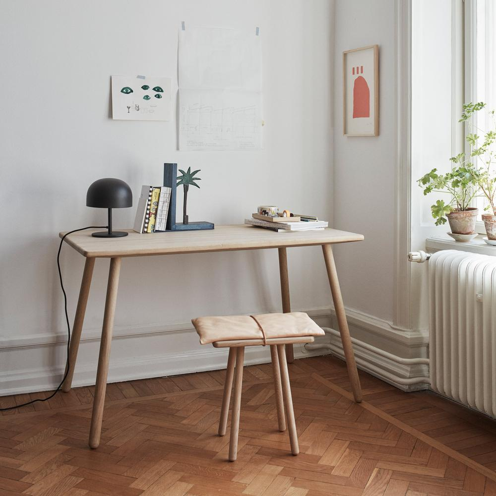 A room with a desk staged with home accents