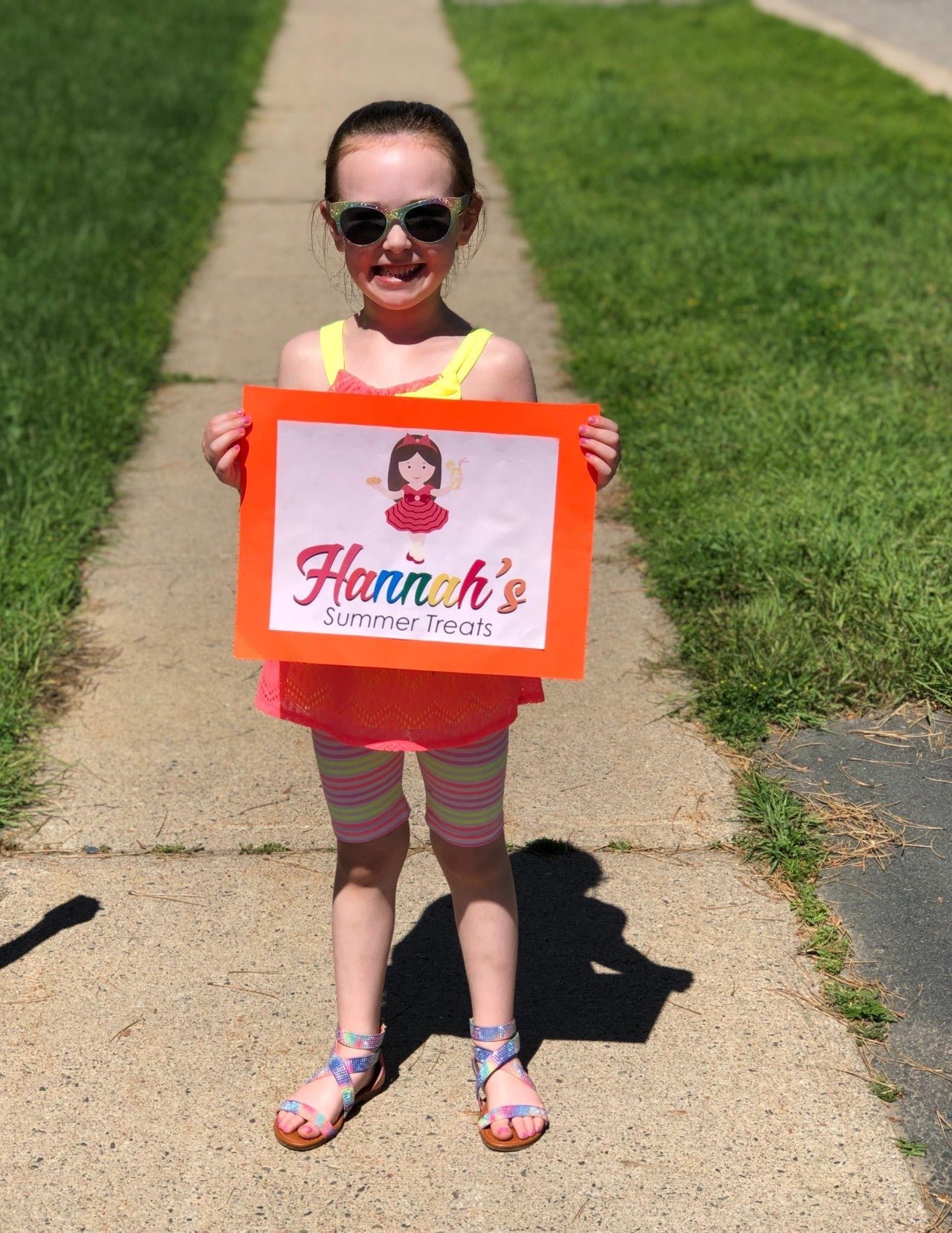 Hannah stands on the sidewalk holding a promotional sign for Hannah's Treats.