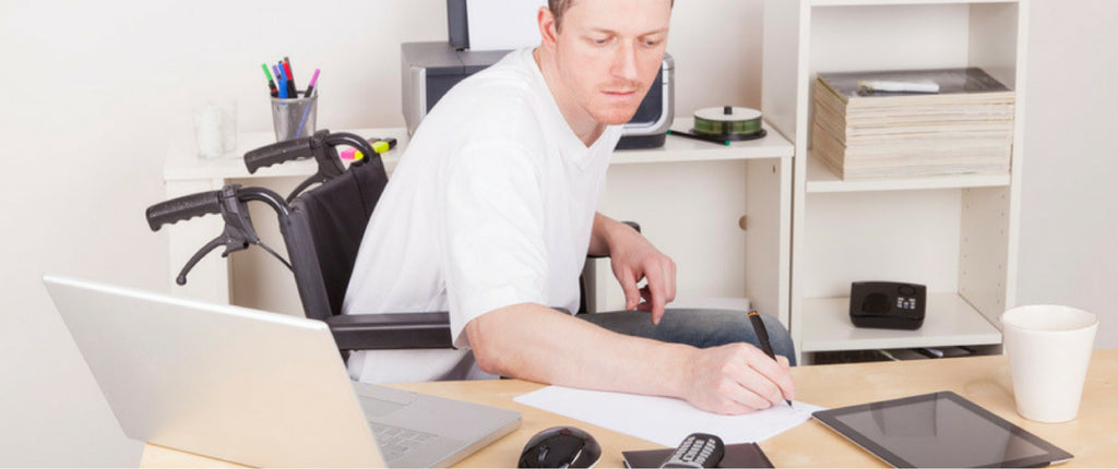 Man in whleechair sitting at desk working