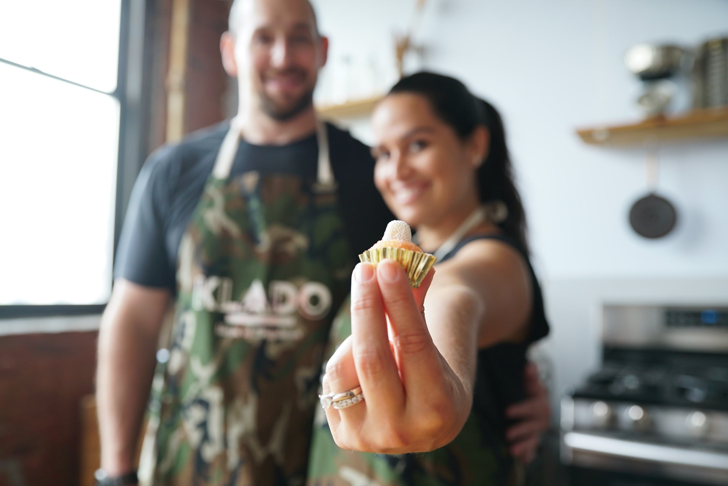 Two people stand, out of focus, wearing aprons. The woman on the right holds out a dessert, in focus in the foreground