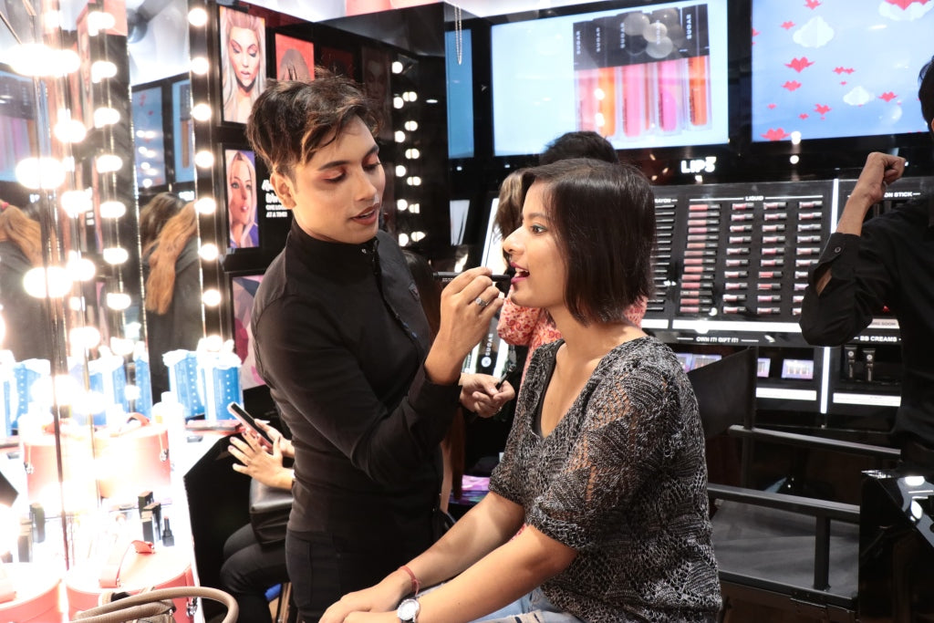 A SUGAR Cosmetics representative helps a customer with a makeover in a retail location.