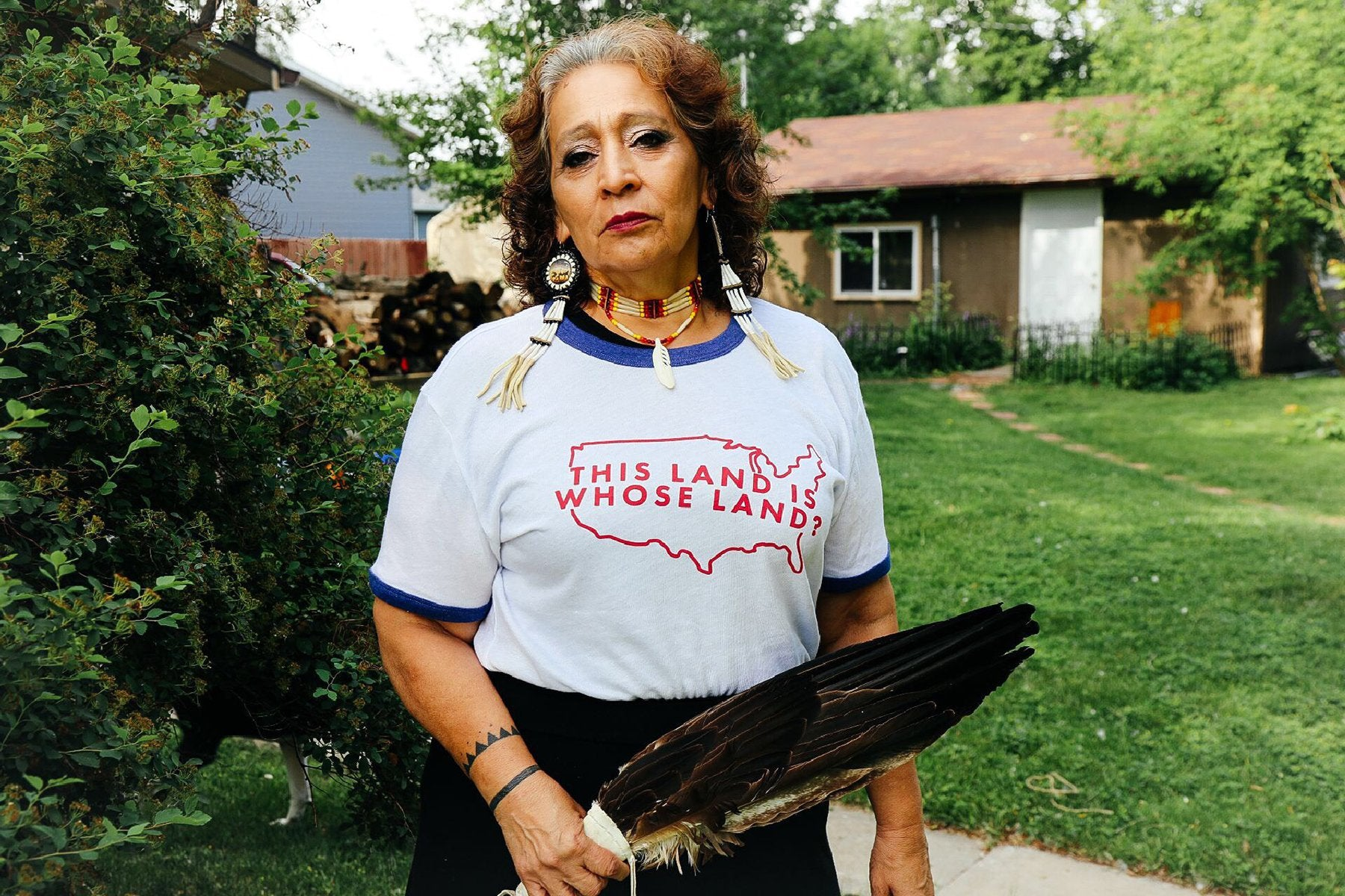 "An Indigenous woman stands in a yard wearing a shirt that reads, ""This land is whose land?"""