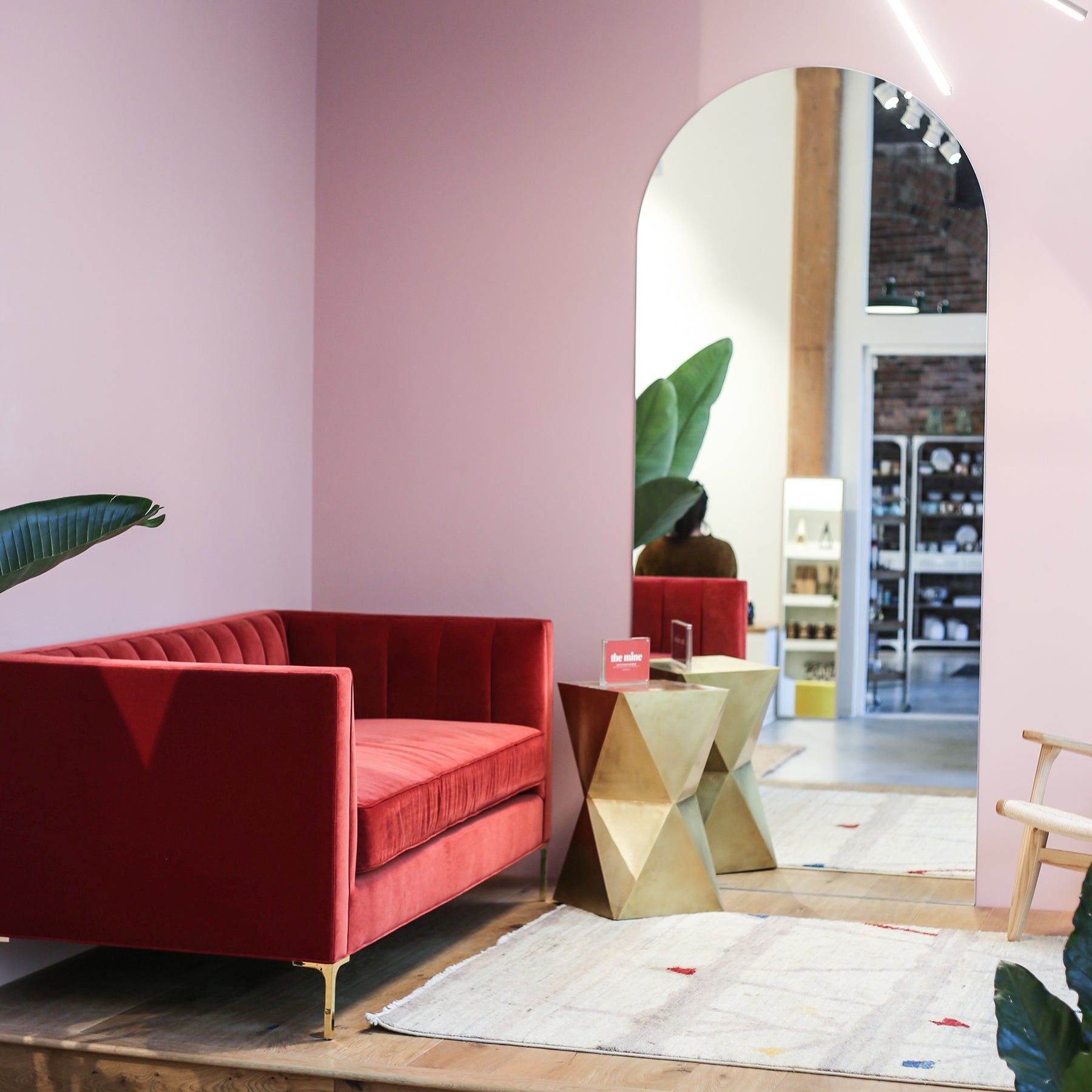 Interior of a store with pink walls and a red couch