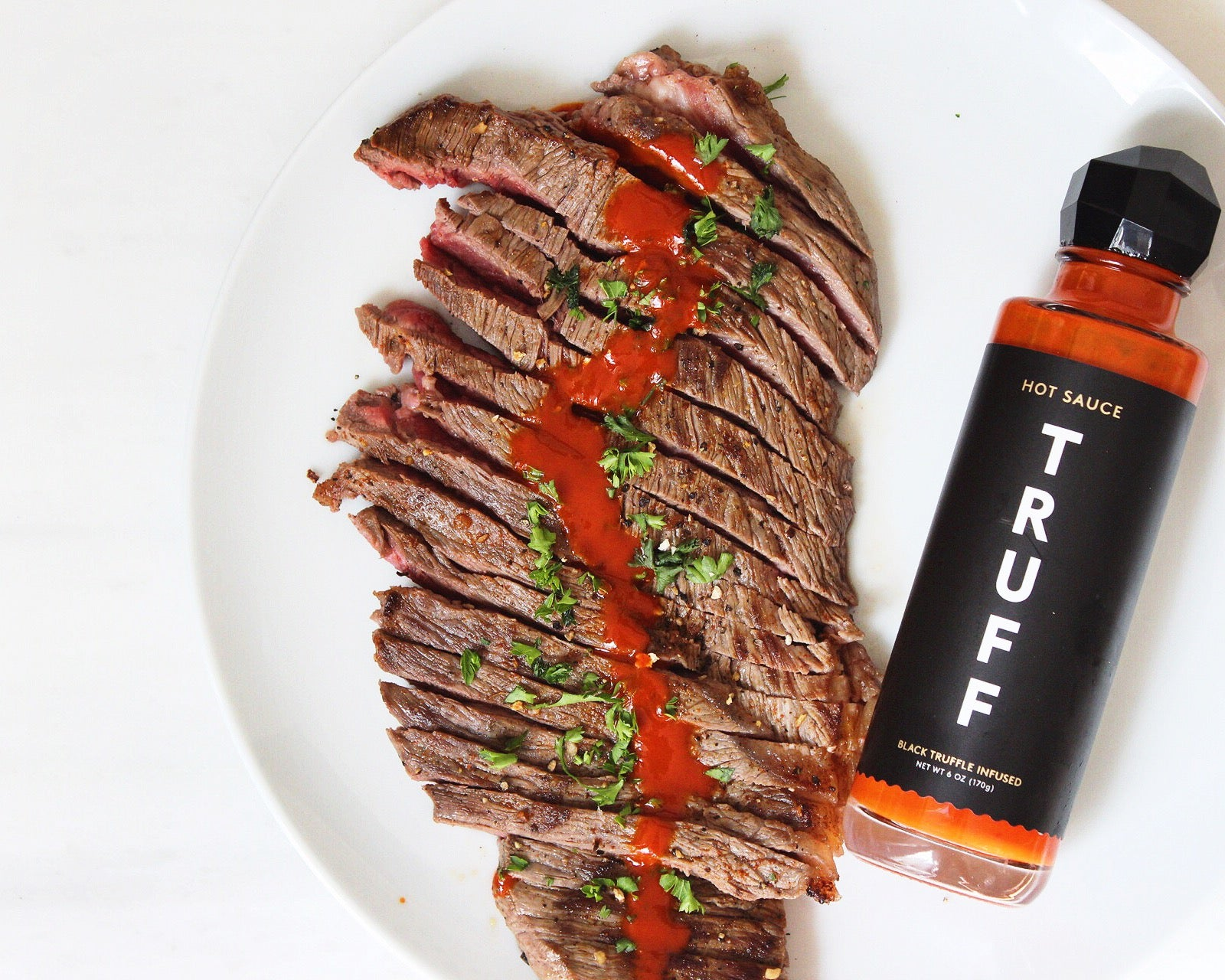 A plate of steak with a bottle of Truff sauce on the side.