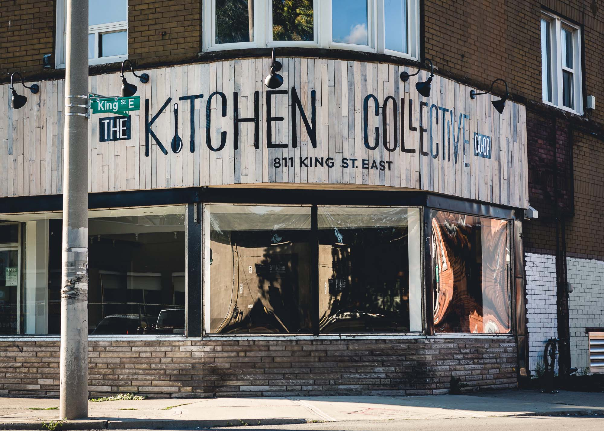 A storefront on the corner of an intersection with a sign that reads Kitchen Collective