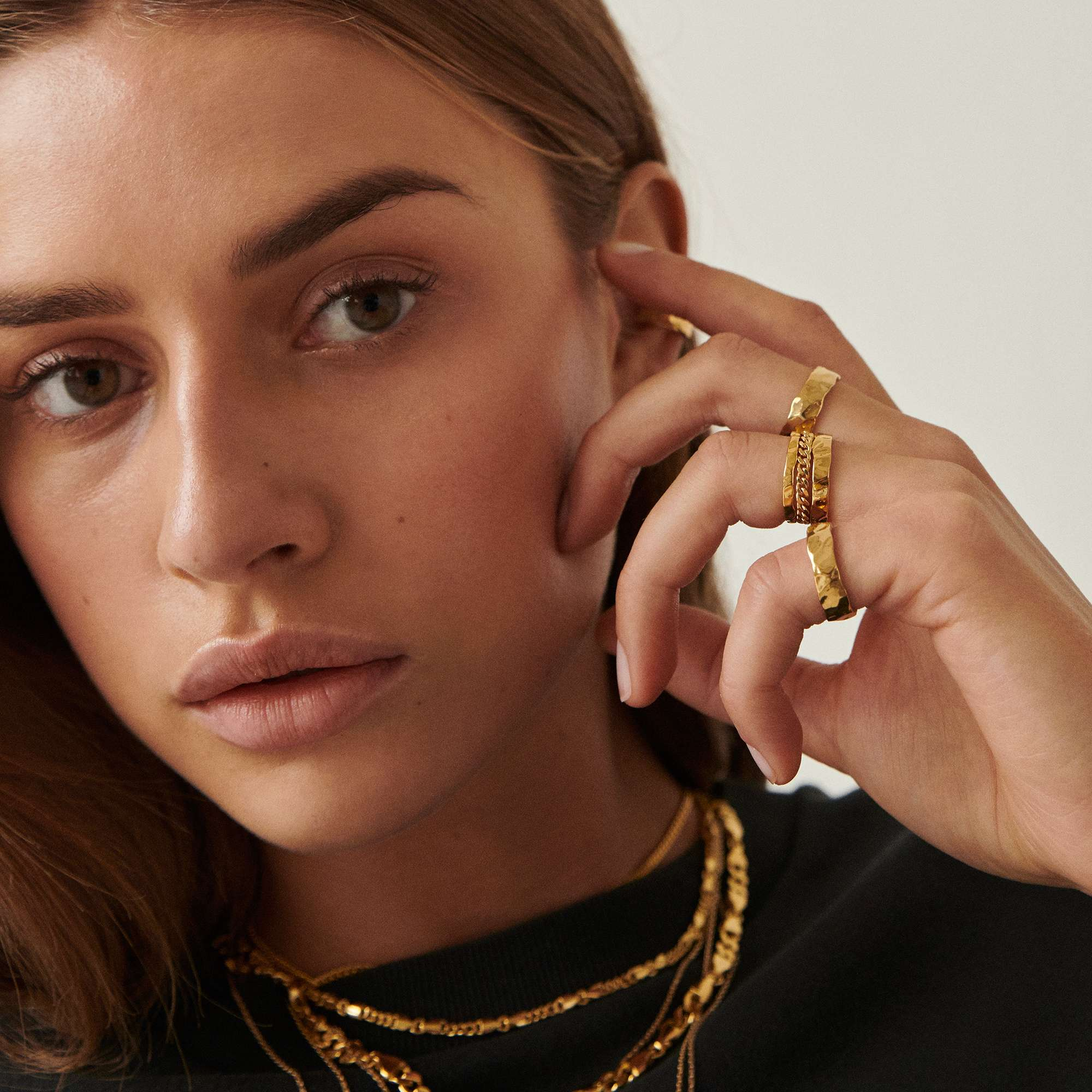 A model in a black shirt wearing multiple necklaces and rings by Camille Brinch.